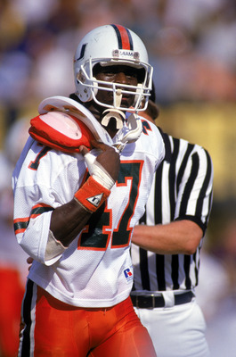 1987:  Wide receiver Michael Irving #47 of the University of Miami Hurricanes runs on the field as he tries to adjust his uniform over his shoulder pads during a 1987 NCAA game. (Photo by Allen Steele/Getty Images)