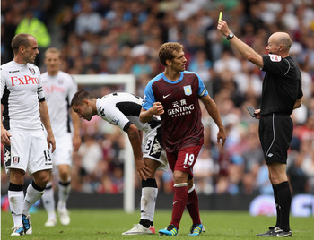 LONDON, ENGLAND - AUGUST 13: Referee Lee Mason shows Stiliyan Petrov of Aston Villa the yellow card after a foul on Clint Dempsey of Fulham during the Barclays Premier League match between Fulham and Aston Villa at Craven Cottage on August 13, 2011 in Lon