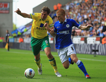 WIGAN, ENGLAND - AUGUST 13:  Grant Holt of Norwich and Ben Foster of Wigan challenge for the ball during the Barclays Premier League match between Wigan Athletic and Norwich City at the DW Stadium on August 13, 2011 in Wigan, England.  (Photo by Matthew L
