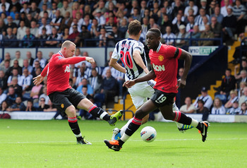 WEST BROMWICH, ENGLAND - AUGUST 14:  Wayne Rooney of Manchester United shoots to score the opening goal during the Barclays Premier League match between West Bromwich Albion and Manchester United at The Hawthorns on August 14, 2011 in West Bromwich, Engla