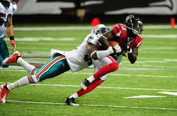 ATLANTA - AUGUST 12: Harry Douglas #83 of the Atlanta Falcons runs with a catch against Nate Ness #32 of the Miami Dolphins during a preseason game at the Georgia Dome on August 12, 2011 in Atlanta, Georgia. (Photo by Scott Cunningham/Getty Images)