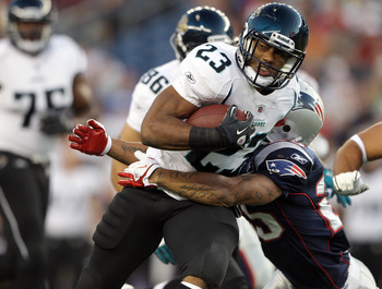 FOXBORO, MA - AUGUST 11:  Rashad Jennings #23 of the Jacksonville Jaguars is hit by Pat Chung #25 of the New England Patriots on August 11, 2011 at Gillette Stadium in Foxboro, Massachusetts.  (Photo by Elsa/Getty Images)
