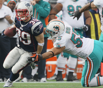 FOXBORO, MA - JANUARY 02:  Danny Woodhead #39 of the New England Patriots tries to avoid Koa Misi #55 of the Miami Dolphins on January 2, 2011 at Gillette Stadium in Foxboro, Massachusetts.  (Photo by Elsa/Getty Images)