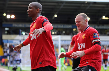 Wayne Rooney prepares to jump Ashley Young