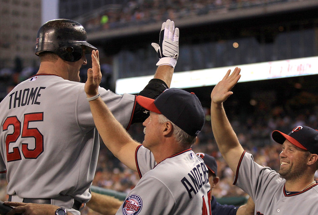 DETROIT, MI - AUGUST 15:  DH, Jim Thome #25 of the Minnesota Twins high-fives teammates in the dug-out after hitting his first of two home runs against the Detroit Tigers during a MLB game at Comerica Park on August 15, 2011 in Detroit, Michigan.  The Twi