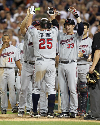 DETROIT, MI - AUGUST 15:  DH, Jim Thome #25 of the Minnesota Twins is congratulated by teammates at home plate after hitting his second home run of the game in the seventh inning and his 600th career home run making him only the eighth player in Major Lea