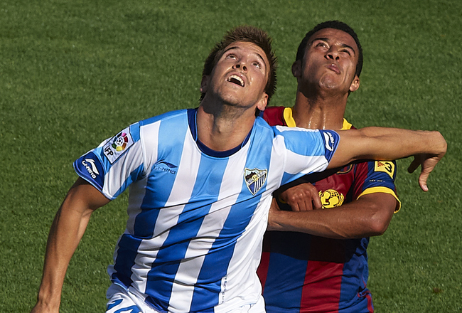 MALAGA, SPAIN - MAY 21:  Thiago (R) of Barcelona competes for the ball with Camacho of Malaga during the La Liga match between Malaga and Barcelona at La Rosaleda Stadium on May 21, 2011 in Malaga, Spain. Barcelona won 3-1.  (Photo by Manuel Queimadelos A