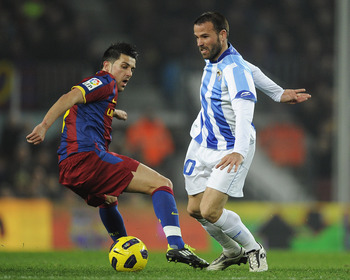 BARCELONA, SPAIN - JANUARY 16:  David Villa of FC Barcelona (L) vies for the ball Apono of Malaga (L) during the La Liga match between FC Barcelona and Malaga at Nou Camp on January 16, 2011 in Barcelona, Spain. Barcelona won 4-1.  (Photo by David Ramos/G
