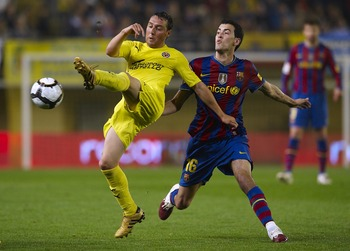 VILLARREAL, SPAIN - MAY 01:  Santi Cazorla of Villarreal CF competes for the ball with Sergio Busquets (R) of FC Barcelona with during the La Liga match between Villarreal CF and FC Barcelona at El Madrigal stadium on May 1, 2010 in Villarreal, Spain.  (P