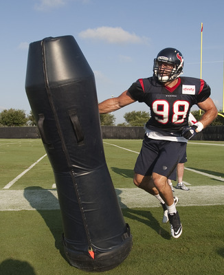 HOUSTON, TX - AUGUST 01:  Outside linebacker Connor Barwin #98 of the Houston Texans hits the tackling dummy during practice on the first day of taining camp at Reliant Park on August 1, 2011 in Houston, Texas.  (Photo by Bob Levey/Getty Images)