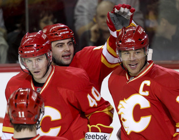 CALGARY, CANADA - APRIL 6:Jarome Iginla #12 of the Calgary Flames is congratulated by teammates Alex Tanguay #40 and Mark Giordano #5 on his hat trick goal against the Edmonton Oilers in third period NHL action on April 6, 2011 at the Scotiabank Saddledom