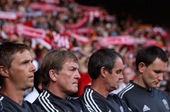 LIVERPOOL, ENGLAND - AUGUST 06:  Liverpool manager Kenny Dalglish with his coaching staff and a sea of Liverpool fans scarfs behind him prior to the pre season friendly match between Liverpool and Valencia at Anfield on August 6, 2011 in Liverpool, Englan