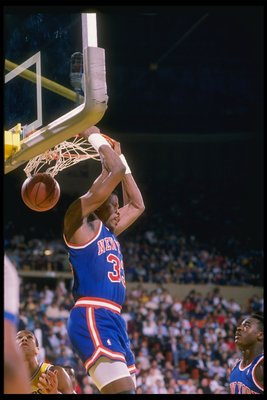 Center Patrick Ewing of the New York Knicks slam dunks.