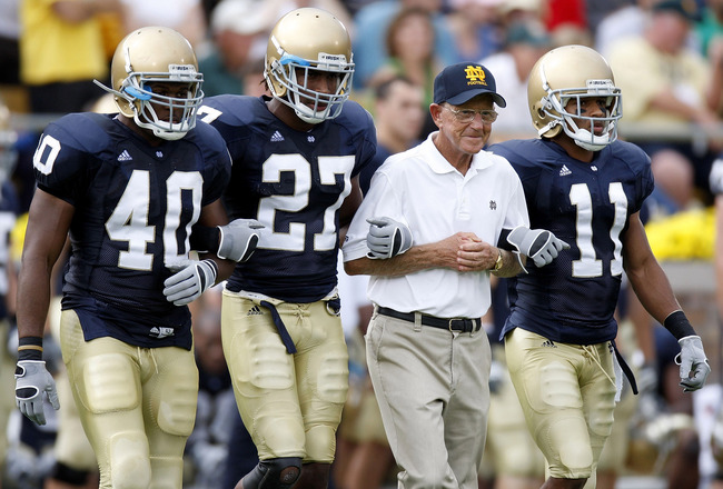SOUTH BEND, IN - SEPTEMBER 13:  Former head coach Lou Holtz of the Notre Dame Fighting Irish walks out for the coin toss with David Grimes #11, David Bruton #27 and Maurice Crum #40 prior to playing the Michigan Wolverines on September 13, 2008 at Notre D
