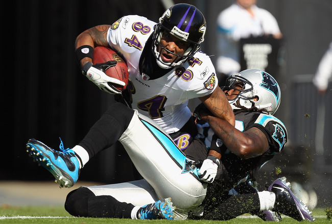 CHARLOTTE, NC - NOVEMBER 21:  T.J. Houshmandzadeh #84 of the Baltimore Ravens scores a touchdown as he is tackled by Charles Godfrey #30 of the Carolina Panthers at Bank of America Stadium on November 21, 2010 in Charlotte, North Carolina.  (Photo by Stre