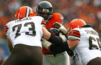 CHICAGO - NOVEMBER 01: Tommie Harris #91 of the Chicago Bears is double-teamed blocked by Joe Thomas #73 and Eric Steinbach #65 of the Cleveland Browns at Soldier Field on November 1, 2009 in Chicago, Illinois. The Bears defeated the Browns 30-6.  (Photo