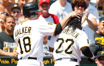 PITTSBURGH, PA - JULY 10:  Neil Walker #18 of the Pittsburgh Pirates congratulates teammates Andrew McCutchen #22 after Walker scored on a sacrifice fly from McCutchen against the Chicago Cubs during the game on July 10, 2011 at PNC Park in Pittsburgh, Pe