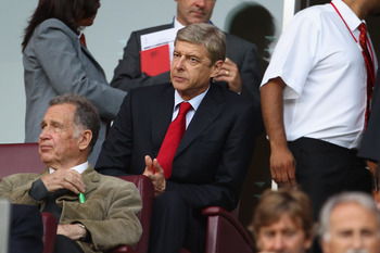 LONDON, ENGLAND - AUGUST 16:  Arsenal manager Arsene Wenger looks on from the stands as he serves a one match touchline ban ahead of the UEFA Champions League play-off first leg match between Arsenal and Udinese at the Emirates Stadium on August 16, 2011