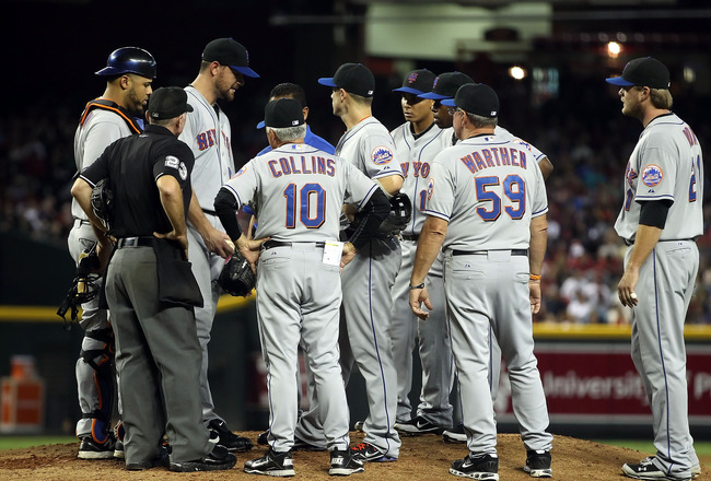 PHOENIX, AZ - AUGUST 13:  Starting pitcher Mike Pelfrey #24 of the New York Mets talks with the team trainer and manager Terry Collins after being hit by a line drive during the fifth inning of the Major League Baseball game against the Arizona Diamondbac
