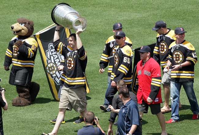 BOSTON, MA  - JUNE 19:  Zdeno Chara of the Boston Bruins hoists the Stanley Cup with his teammates before a game between the Boston Red Sox and the Milwaukee Brewers at Fenway Park on June 19, 2011 in Boston, Massachusetts.  (Photo by Jim Rogash/Getty Ima