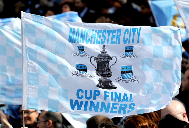 MANCHESTER, ENGLAND - MAY 23:  A Manchester City fan waves a flag during the Manchester City FA Cup Winners Parade at Manchester Town Hall on May 23, 2011 in Manchester, United Kingdom.  (Photo by Chris Brunskill/Getty Images)