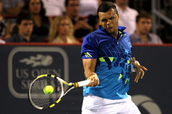 MONTREAL, QC - AUGUST 13:  Jo-Wilfried Tsonga of France returns a shot to Novak Djokovic of Serbia during the Rogers Cup at Uniprix Stadium on August 13, 2011 in Montreal, Canada.  (Photo by Matthew Stockman/Getty Images)