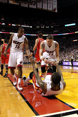 MIAMI, FL - MAY 24:  Mario Chalmers #15 and Mike Miller #13 of the Miami Heat react as they help up Udonis Haslem #40 of the Miami Heat against the Chicago Bulls  in Game Four of the Eastern Conference Finals during the 2011 NBA Playoffs on May 24, 2011 a