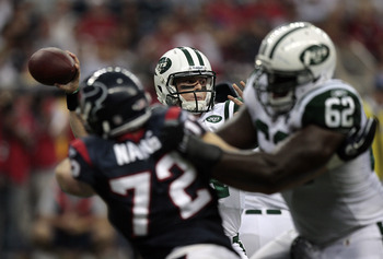 HOUSTON - AUGUST 15:  Quarterback Greg McElroy #14 of the New York Jets looks for a receiver as offensive lineman Vladimir Ducasse #62 blocks outside linebacker Jesse Nading  #72 of the Houston Texans at Reliant Stadium on August 15, 2011 in Houston, Texa