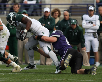EVANSTON, IL - OCTOBER 23: Edwin Baker #4 of the Michigan State Spartans tries to break away from Vince Browne #94 of the Northwestern Wildcats at Ryan Field on October 23, 2010 in Evanston, Illinois. Michigan State defeated Northwestern 35-27.  (Photo by