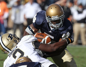 SOUTH BEND, IN - SEPTEMBER 04: Armando Allen Jr. #5 of the Notre Dame Fighting Irish is tackled by Gerald Gooden #2 of the Purdue Boilermakers at Notre Dame Stadium on September 4, 2010 in South Bend, Indiana. Notre Dame defeated Purdue 23-12.  (Photo by