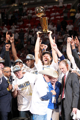 MIAMI, FL - JUNE 12:  Finals MVP Dirk Nowitzki #41 of the Dallas Mavericks celebrates with the Larry O'Brien Championship trophy along with Brendan Haywood #33, Caron Butler and team owner Mark Cuban after the Mavericks won 105-95 against the Miami Heat i