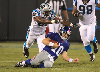 CHARLOTTE, NC - AUGUST 13:  Eli Manning #10 of the New York Giants is tackled by Bryant Browning #63 of the Carolina Panthers during their preseason game at Bank of America Stadium on August 13, 2011 in Charlotte, North Carolina.  (Photo by Streeter Lecka