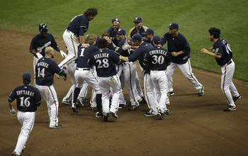 MILWAUKEE, WI - AUGUST 16: Mark Kotsay #25 of the Milwaukee Brewers is swarmed by teammates after hitting the game winning RBI single against the Los Angeles Dodgers in the ninth inning at a Major League Baseball game at Miller Park Stadium on August 16,