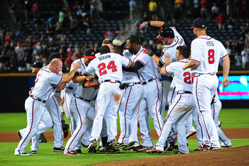 ATLANTA - AUGUST 16: Martin Prado #14 of the Atlanta Braves is mobbed by teammates after knocking in the game-winning run in the 11th inning against the San Francisco Giants at Turner Field on August 16, 2011 in Atlanta, Georgia. (Photo by Scott Cunningha