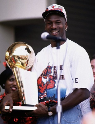 18 Jun 1996: Michael Jordan of the Chicago Bulls poses with the NBA championship trophy at the Bulls'' 1996 victory parade in Chicago, Illinois, after the Bulls won their 4th NBA championship in 6 years with a record of 83-13. Jordan, whose contract ends