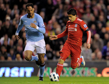 LIVERPOOL, ENGLAND - APRIL 11:  Luis Suarez of Liverpool is pursued by Joleon Lescott of Manchester City during the Barclays Premier League match between Liverpool and Manchester City at Anfield on April 11, 2011 in Liverpool, England. (Photo by Michael R