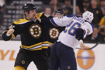 BOSTON - NOVEMBER 06:  Mark Stuart #45 of the Boston Bruins and BJ Crombeen #26 of the St. Louis Blues fight in the second period on November 6, 2010 at the TD Garden in Boston, Massachusetts.  (Photo by Elsa/Getty Images)