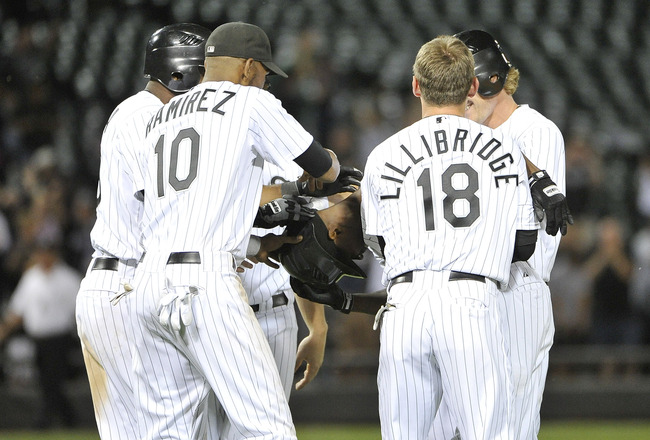 CHICAGO, IL - AUGUST 17:  Juan Pierre #1 (C) of the Chicago White Sox is mobbed by Alexei Ramierez #10, Brent Lillibridge #18 and other teammates after hitting a game-winning RBI single scoring Gordon Beckham against the Clevland Indians during the 14th i