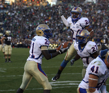 SOUTH BEND, IN - OCTOBER 30: John Flanders #21 of the Tulsa Golden Hurricane holds the ball after intercepting a pass in the end zone in the final minute of play against the Notre Dame Fighting Irish as teammates Charles Davis #24 and DeWitt Jennings #27