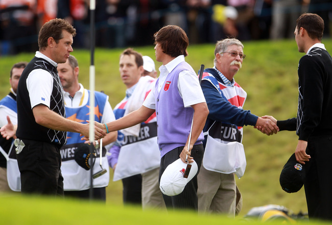 NEWPORT, WALES - OCTOBER 02: Lee Westwood of Europe (L) shakes hands with Rickie Fowler of the USA as caddie Mike Cowan shakes hands with Martin Kaymer on the 18th green after they halved their match during the rescheduled Afternoon Foursome Matches durin