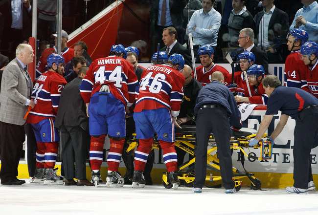 MONTREAL, CANADA - MARCH 8:  Members of the Montreal Canadiens medical staff and players put Max Pacioretty #67 of the Montreal Canadiens on a stretcher after being body checked by Zdeno Chara #33 of the Boston Bruins (not pictured) during the NHL game at