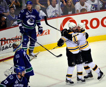 VANCOUVER, BC - JUNE 15:  Patrice Bergeron #37 of the Boston Bruins celebrates with Gregory Campbell #11 after he scored the 3rd goal in the second period as Roberto Luongo #1, Christian Ehrhoff #5 and Alexander Edler #23 of the Vancouver Canucks look on