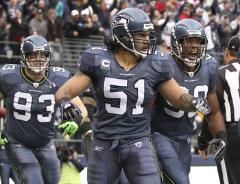 SEATTLE, WA - DECEMBER 05:  Linebacker Lofa Tatupu #51 of the Seattle Seahawks celebrates with Jay Richardson #99 and Craig Terrill #93 after returning an interception for a touchdown against the Carolina Panthers at Qwest Field on December 5, 2010 in Sea