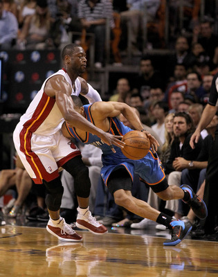 MIAMI, FL - MARCH 16:  Russell Westbrook #0 of the the Oklahoma City Thunder dribbles into Dwyane Wade #3 of the Miami Heat during a game at American Airlines Arena on March 16, 2011 in Miami, Florida. NOTE TO USER: User expressly acknowledges and agrees