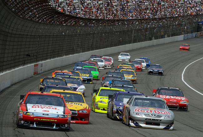 BROOKLYN, MI - JUNE 19:  Greg Biffle, driver of the #16 American Red Cross Ford, and Brian Vickers, driver of the #83 Red Bull Toyota, lead the field after a restart during the NASCAR Sprint Cup Series Heluva Good! Sour Cream Dips 400 at Michigan Internat