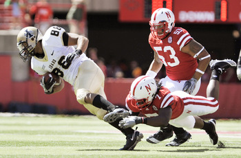 LINCOLN, NEBRASKA - SEPTEMBER 11: Nebraska Cornhuskers defensive back DeJon Gomes #7 trips up Idaho Vandals wide receiver Daniel Hardy #88 during second half action of their game at Memorial Stadium on September 4, 2010 in Lincoln, Nebraska. Nebraska defe