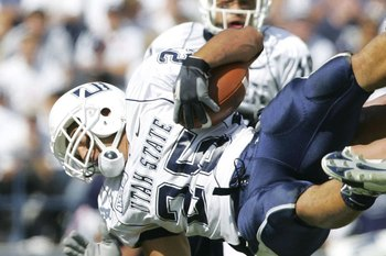 PROVO, UT - SEPTEMBER 23:   Lynwood Johnson #25 of Utah State is tackled by Ben Criddle #25 and Aaron Wagner #52 of BYU September 23, 2006 in Provo, Utah. BYU defeated Utah State 38-0.  (Photo by Kent Horner/Getty Images)