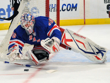 NEW YORK - FEBRUARY 14:  Goalie Henrik Lundqvist #30 of the New York Rangers loses his stick as he dives out of the crease to cover the puck against the Tampa Bay Lightning during the first period of an NHL game at Madison Square Garden on February 14, 20