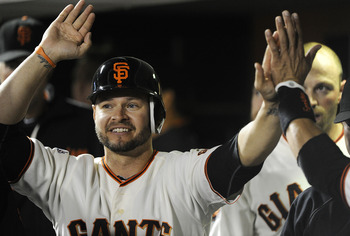 SAN FRANCISCO, CA - AUGUST 9: Cody Ross #13 of the San Francisco Giants celebrates after scoring on an RBI single by Orlando Cabrera #43 against the Pittsburgh Pirates in eighth inning during an MLB baseball game at AT&T Park August 9, 2011 in San Francis