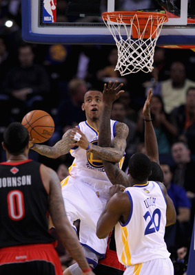 OAKLAND, CA - MARCH 25: Monta Ellis #8 of the Golden State Warriors is fouled while going up for a shot against the Toronto Raptors at Oracle Arena on March 25, 2011 in Oakland, California. NOTE TO USER: User expressly acknowledges and agrees that, by dow